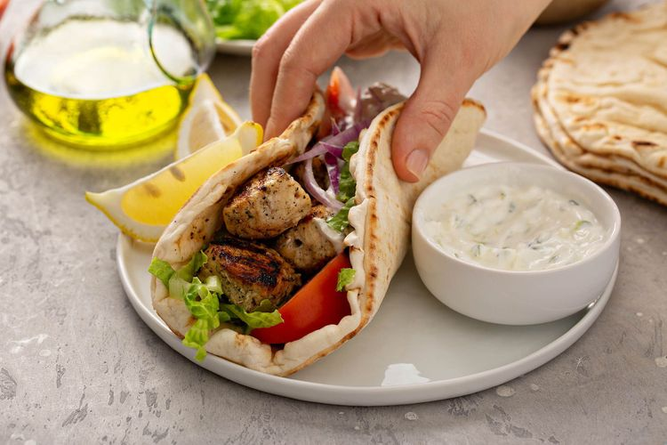 Chicken souvlaki with fresh vegetables on a flatbread with tzatziki sauce © Elena Veselova/Shutterstock