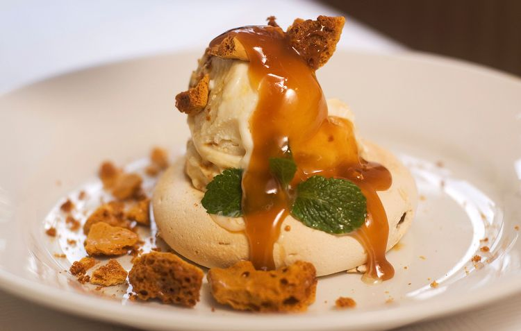 A caramel puff candy meringue dessert with ice cream on a plate ready to be served.