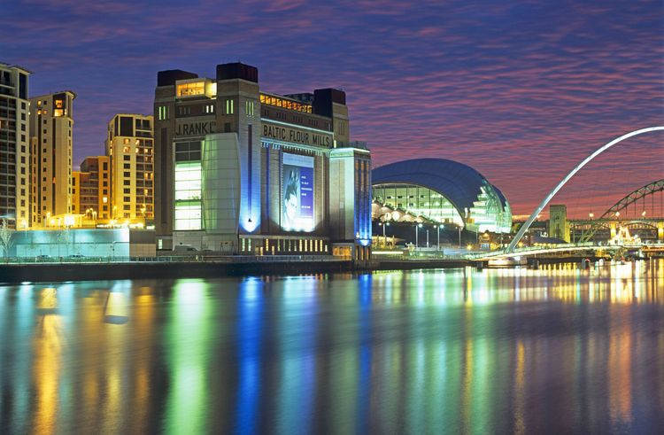 The lights of the Baltic Arts and the Sage Music Centres reflect in the River Tyne at night. Tyne & Wear, England, UK