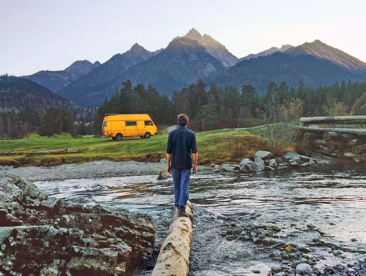 Man traveler with yellow van camping in mountains travel adventure healthy lifestyle summer vacations