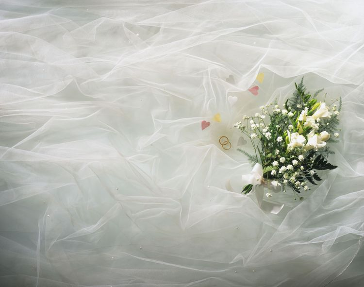 White flower bouquet on tulle, hearts and gold rings visible through fabric
